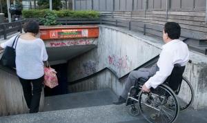 Persona disabile in difficoltà di fronte ad una fermata della Metropolitana di Roma